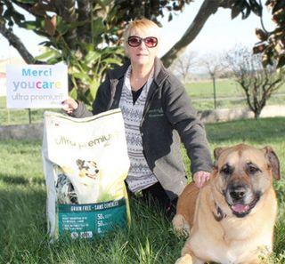 Personne et chien devant un paquet de croquettes Ultra Premium Direct avec une pancarte Merci T