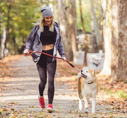 Une femme courant avec son chien dans un parc